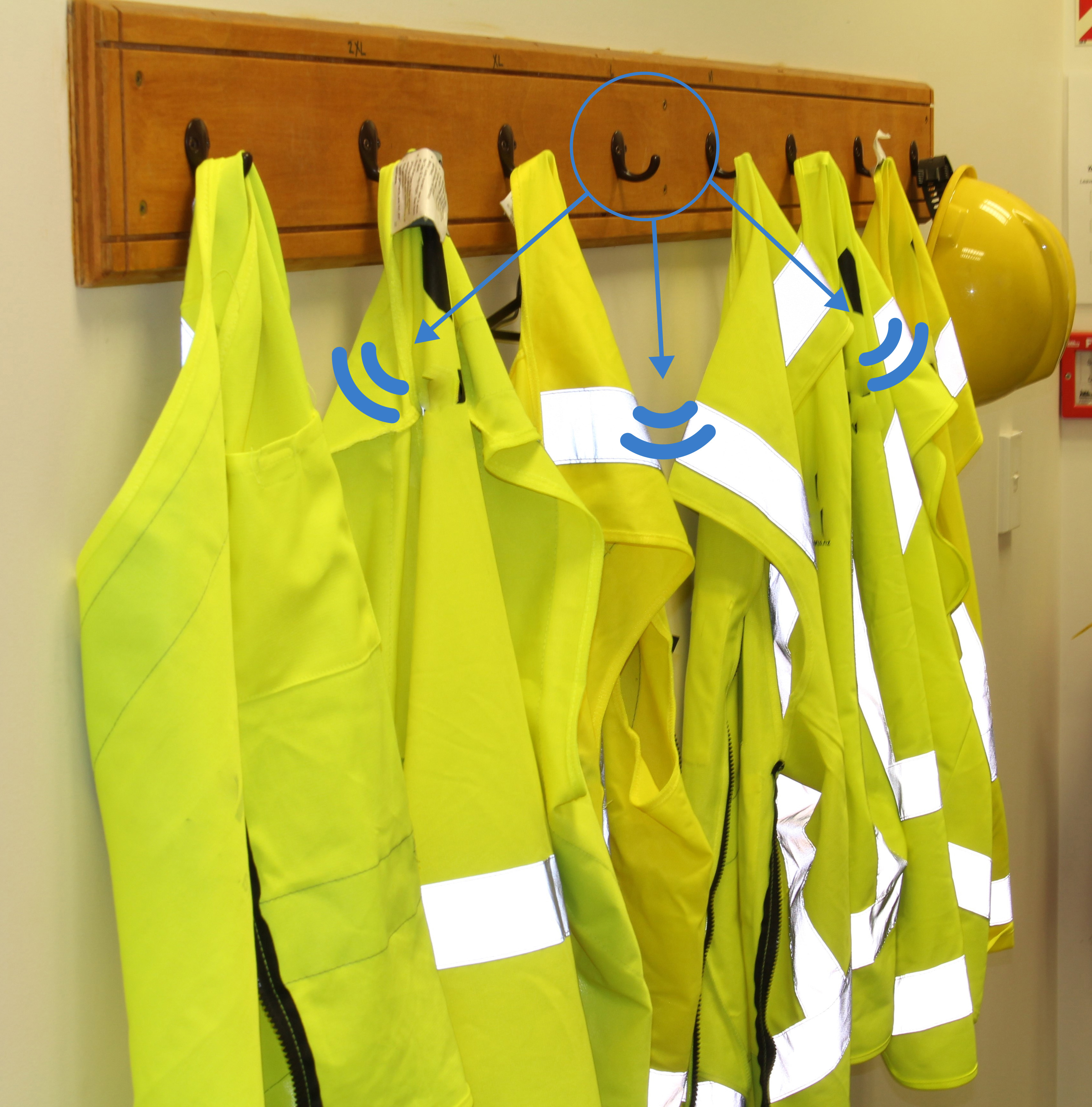 High visibility jackets charging on a coat rack embedded with Powercast's wireless charging technology